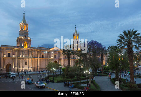 Basilica Cathedral of Arequipa in the Plaza de Armas, Arequipa, Peru, floodlit in evening light with El Misti volcano - Stock Photo