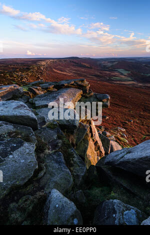 A cold, windy sunset on Stanage Edge in the Peak District, Derbyshire.  Frosty Gritstone features dominate the foreground. - Stock Photo