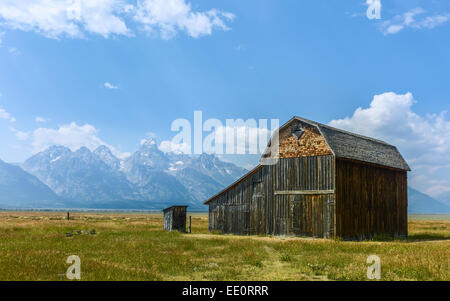 Derelict barns of early Mormon community set against the Grand Tetons on a bright sunny day, Mormon Row, Packston, - Stock Photo
