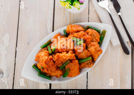 pieces of chicken in batter with spicy sauce and green beans - Stock Photo