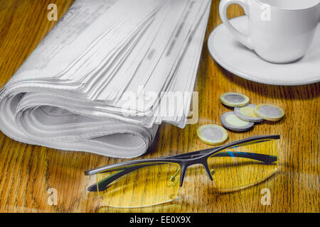 newspaper cup of coffee and glasses on the table Coins morning news - Stock Photo