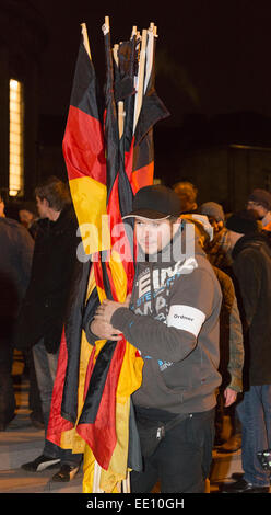 05/01/2015. Cologne, Germany. A right-wing protester clutches German national flags before handing them out to supporters. - Stock Photo