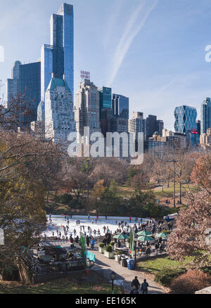 Trump Rink in Central Park on a sunny snow free day. The former Wollman Rink hosts skaters below the towering city - Stock Photo