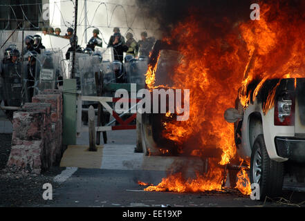 Guerrero, Mexico. 12th Jan, 2015. Flames emanate from a vehicle during a protest in front of the 35th Military Zone - Stock Photo