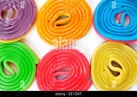 some licorice wheels of different colors on a white background - Stock Photo