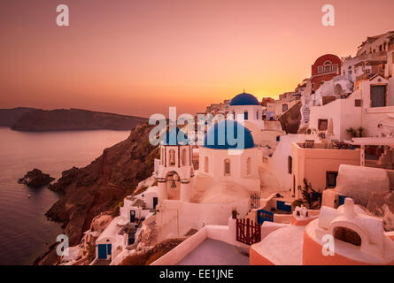 Greek church with three blue domes at sunset, Oia, Santorini (Thira), Cyclades Islands, Greek Islands, Greece, Europe - Stock Photo