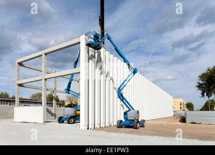 Cranes working on the columns of a building under construction - Stock Photo