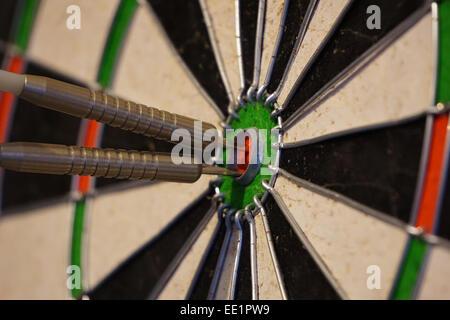 Two darts in the bulls eye of a dart board. - Stock Photo