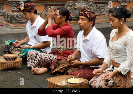 Several people pray and leave offerings in the Holy Monkey Forest during the celebration of Galungan. Galungan festival, - Stock Photo