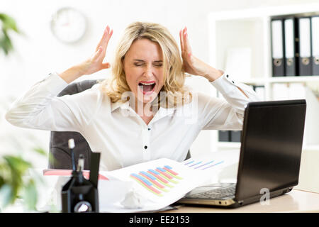 Stressed business woman screaming loudly working in office - Stock Photo