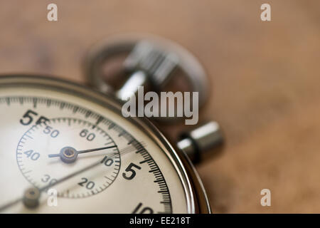 old silver chrome stopwatch with seconds and minute hands 5 second count down chronological timer glass dial buttons against