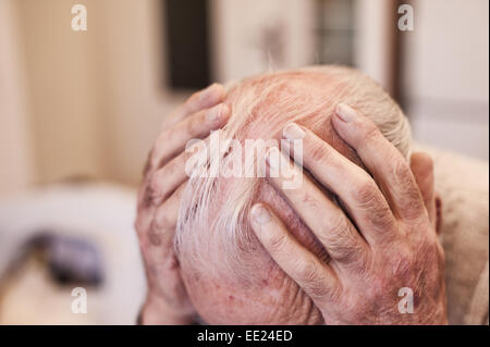 Holding ones head deep in though worrying and contemplating the sadness and happiness of previous times memories - Stock Photo