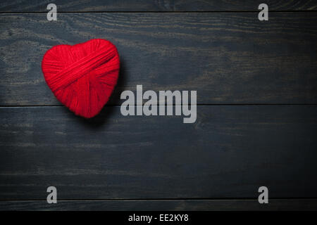 Valentine's Day background with heart made of red wool. Copy space. Top view - Stock Photo
