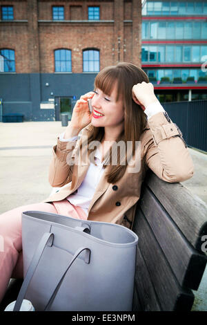 Young woman using phone outdoors, Munich, Bavaria, Germany - Stock Photo