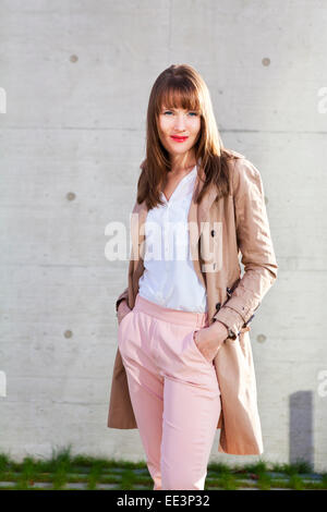 Young woman with hands in pockets standing outdoors, Munich, Bavaria, Germany - Stock Photo
