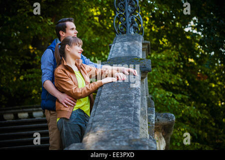 Young couple standing on staircase outdoors, Munich, Bavaria, Germany - Stock Photo