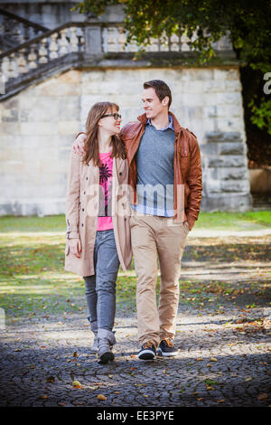 Happy young couple walking through park, Munich, Bavaria, Germany - Stock Photo