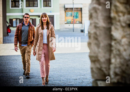 Young couple walking through Old Town, Munich, Bavaria, Germany - Stock Photo
