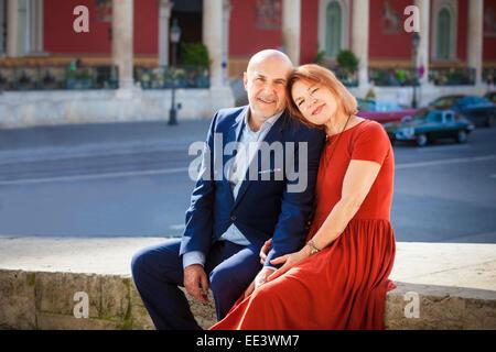 Happy senior couple sitting side by side outdoors, Munich, Bavaria, Germany - Stock Photo