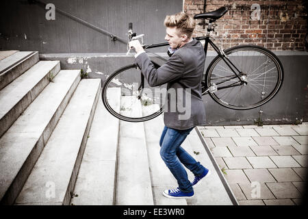 Young businessman carrying bicycle across stairs, Munich, Bavaria, Germany - Stock Photo