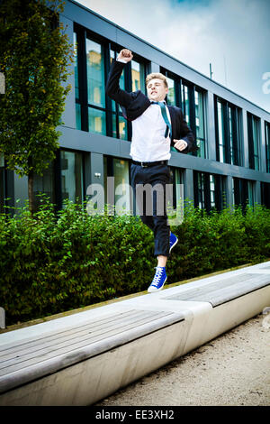 Young businessman jumps in air cheering, Munich, Bavaria, Germany - Stock Photo