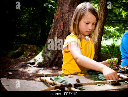 Schoolgirl crafting in a forest camp, Munich, Bavaria, Germany - Stock Photo