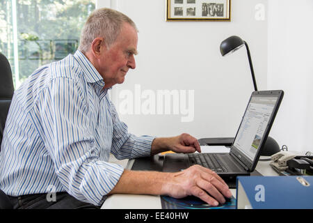 Senior man in his 70s sitting at home on the computer, laptop, - Stock Photo