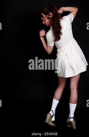 cute pretty young woman strikes a pose in a retro 1950's dress. 30th April 2013 - Stock Photo