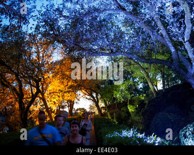 Visitors to a candlelight night at the gardens of Chateau Marqueyssac walk through the illuminated parks at dusk. - Stock Photo