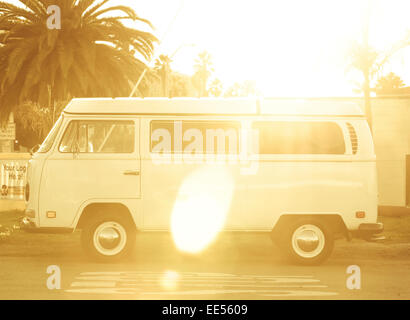A vintage white westfalia parked on the side of the road in front of a palm tree with a lot of sun blasting through - Stock Photo