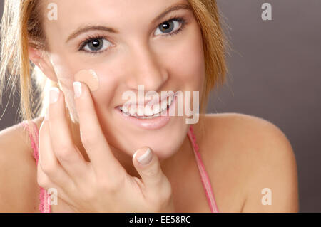 This stock photo shows a young woman applying foundation make-up or concealer. - Stock Photo