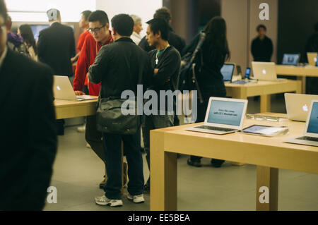 people are trying out apple tablet, ipad mini and all kind of apple gadgets in Apple Store in Hong Kong IFC. - Stock Photo