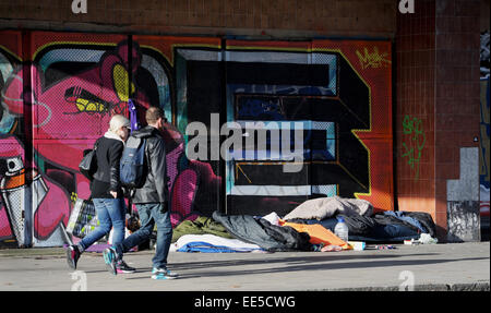 Brighton UK - People pass by boxes and bedding belonging to rough sleepers under the entrance of The Astoria in - Stock Photo