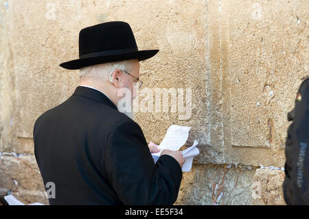 A jewish man is reading from a paper in front of the western wall in the old city of Jerusalem - Stock Photo