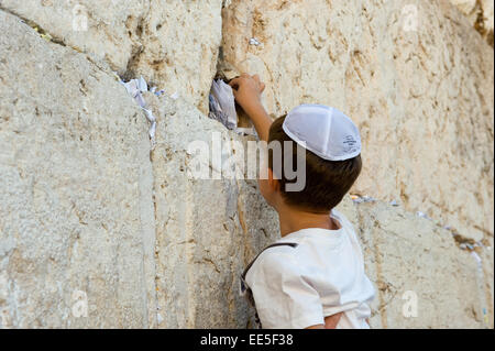 JERUSALEM, ISRAEL - OCT 06, 2014: A young jewish boy is putting a paper with a wish in a crack between the stones - Stock Photo