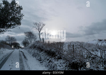 View landscape scene of snowy country road and snow ice on rural roads in countryside in winter with hedgerow Carmarthenshire - Stock Photo