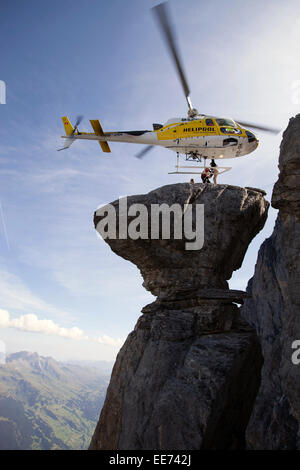 A helicopter is hovering over a spectacular rock. Thereby a BASE jumper is getting out of the cabin. He will jump - Stock Photo