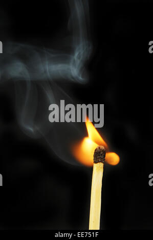 Igniting match flame and smoke against a black background - Stock Photo