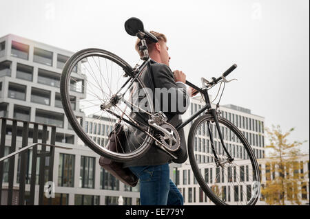 Young businessman carrying bicycle, Munich, Bavaria, Germany - Stock Photo