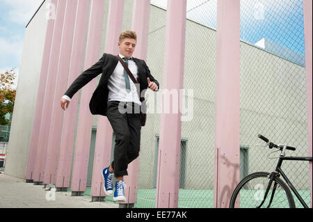 Young businessman jumping in air, Munich, Bavaria, Germany - Stock Photo