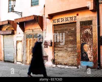 Man dressed in traditional garment walking on the street in early morning - Marrakesh, Morocco - Stock Photo