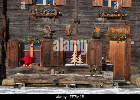Christmas decorations decorating Swiss wooden chalet in the Alps in winter, Wallis / Valais, Switzerland - Stock Photo