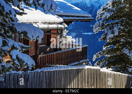 Snow covered Swiss wooden chalet in winter in the Alps, Wallis / Valais, Switzerland - Stock Photo