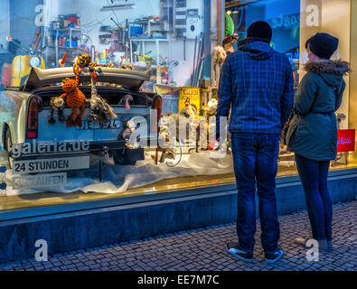 Couple admiring Christmas toy display in window of Galeria Kaufhof, Department store, Alexanderplatz, Mitte, Berlin, - Stock Photo