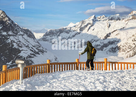 Tourist in the snow looking over the mountains in winter surrounding the Swiss Aletsch Glacier, largest in the Alps, - Stock Photo
