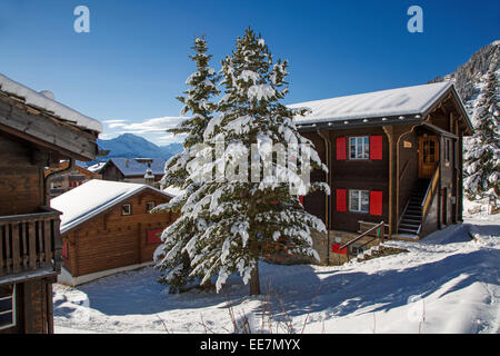 Swiss wooden chalets in the snow in winter in the Alps, Wallis / Valais, Switzerland - Stock Photo