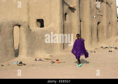 A girl walks past a mosque in a village near Djenne, Mali - Stock Photo