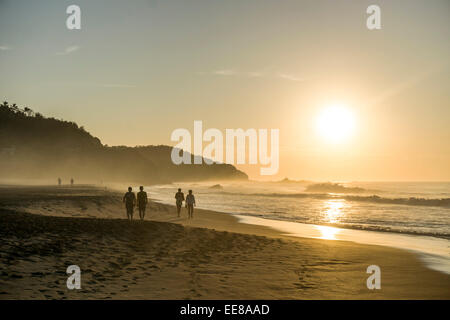 San Agustinillo in Oaxaca State, Mexico. 14th January, 2014. people walking on beautiful sandy beach as sun rises - Stock Photo