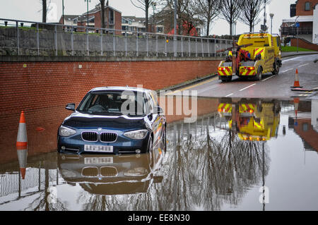 A towtruck arrives to rescue a stranded BMW car from floodwater. - Stock Photo