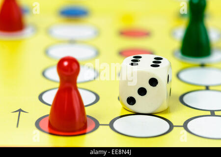 Pieces and a die on a Ludo board game - Stock Photo